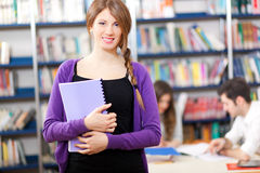 Woman holding a book in a library Stock Photography