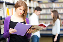 Woman holding a book in a library Royalty Free Stock Photo