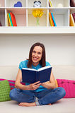 Woman holding book and looking at camera Royalty Free Stock Image