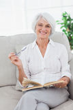 Woman holding a book and looking at camera Royalty Free Stock Photo