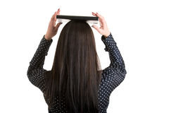 Woman Holding a Book Over Her Head. To show the concept of elegance, viewed from the back, isolated in white Stock Image