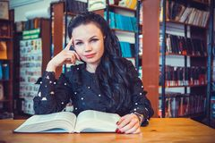 Woman holding book posing for camera at library Royalty Free Stock Photos