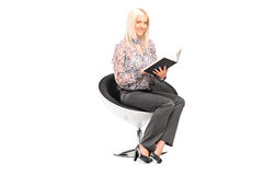 Woman holding book seated on a modern chair Stock Photography
