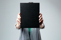 Woman holding a book and showing blank black cover Stock Image