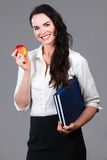 Woman holding books and apple. Portrait of a confident attractive business woman holding book and an apple Royalty Free Stock Images