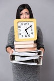Woman holding books, folders and wall clock Stock Photography