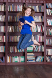 Woman holding books and jumping Stock Photo
