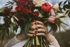 Woman holding boquet. Bride with red nails holding boquet Royalty Free Stock Photo
