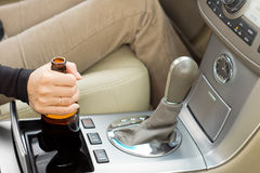 Woman holding a bottle of alcohol while driving Royalty Free Stock Photo