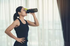 A woman holding a bottle of protein supplements on muscle drink. To strengthen health care to vigorous and beautiful royalty free stock photos