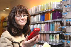 A woman holding bottle of shampoo Stock Photos