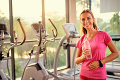 Woman holding bottle of water in gym. Healthy lifestyle and sport. Pretty young woman holding bottle of water in gym Royalty Free Stock Image