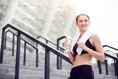 Woman holding a bottle of water. Nice weather for jogging. Contended pretty young woman holding a bottle of water and a towel after working out in the city Stock Image