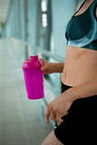 Woman holding bottle of water, taking a break from exercise. Stock Photos