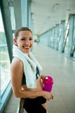 Woman holding bottle of water, taking a break from exercise. Royalty Free Stock Photography
