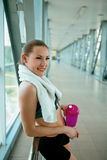 Woman holding bottle of water, taking a break from exercise. Stock Images