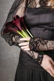 Woman holding bouquet of black calla flowers (Zantedeschia) Stock Photos