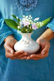 Woman holding bouquet of flower in vase. Blue clothing background Royalty Free Stock Photo