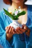 Woman holding bouquet of flower in vase. Blue clothing background Stock Image