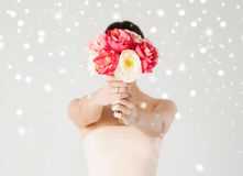 Woman holding bouquet of flowers over her face Stock Image