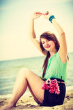 Woman holding bouquet of flowers sitting on beach Stock Photography