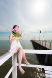 Woman holding bouquet of flowers sitting on pier Stock Photo
