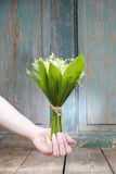 Woman holding bouquet of lily of the valley flowers Royalty Free Stock Image