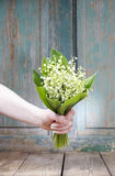 Woman holding bouquet of lily of the valley flowers Stock Photos