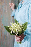 Woman holding bouquet of lily of the valley flowers Royalty Free Stock Photography