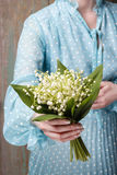 Woman holding bouquet of lily of the valley flowers Stock Images