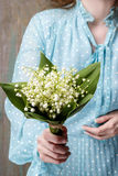 Woman holding bouquet of lily of the valley flowers Royalty Free Stock Photos