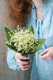 Woman holding bouquet of lily of the valley flowers Royalty Free Stock Images
