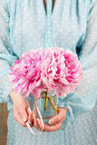 Woman holding bouquet of pink peonies Stock Photo