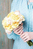 Woman holding bouquet of yellow carnation and pink pastel roses Stock Photo