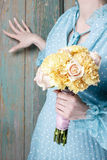 Woman holding bouquet of yellow carnation and pink roses Stock Photos