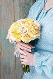Woman holding bouquet of yellow carnation and pink roses Royalty Free Stock Photo