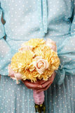 Woman holding bouquet of yellow carnation and pink roses Royalty Free Stock Photos