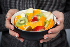 Woman holding bowl of fresh fruit stock photography