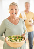 Woman Holding Bowl Of Salad With Man At Home Royalty Free Stock Photo