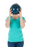 Woman is holding a bowling ball just before her head Royalty Free Stock Image