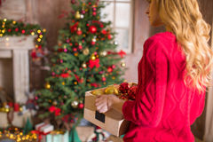 Woman holding box with baubles. Young blonde woman holding box with shiny baubles Stock Images
