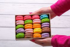 Woman holding box with colourful macaroons. Dessert. Summer travel vacation in French Riviera. Woman holding box with colourful macaroons over white wooden royalty free stock photography