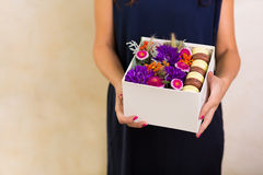 Woman holding a box with flowers and macaroon cookies Stock Photography