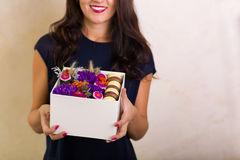 Woman holding a box with flowers and macaroon cookies Stock Photos