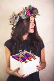 Woman holding a box with flowers and macaroon cookies Stock Images