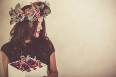 Woman holding a box with flowers and macaroon cookies Royalty Free Stock Images