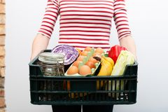 Woman holding box of grocery food and from store. Online grocery shopping service concept. In a natural light royalty free stock image
