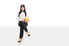 Woman holding a box of popcorn seated on panel Royalty Free Stock Photography