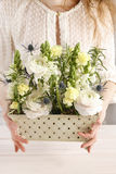 Woman holding box with ranunculus and matthiola flowers Stock Photo