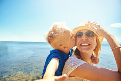 Woman holding boy on back kissing her. Pretty mother smiling and holding son on back that kissing her on cheek on background of seashore royalty free stock photography